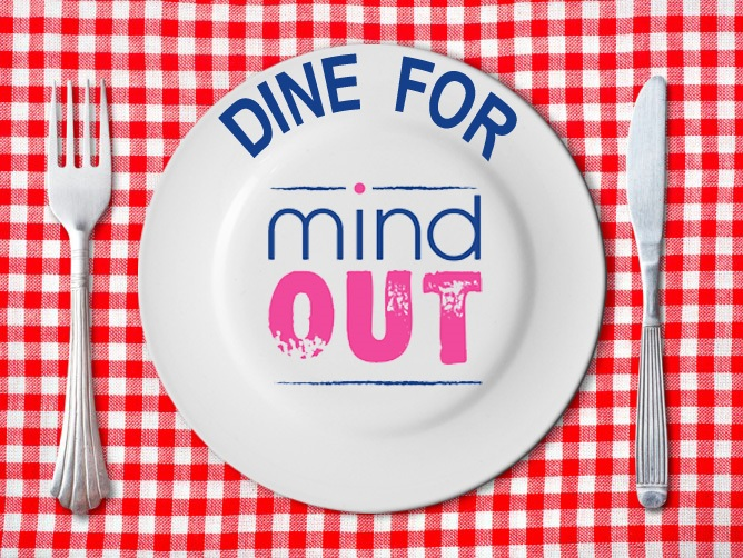 "a plate on a red check table cloth with ""dine for mindout"" written on it in coloured writing"