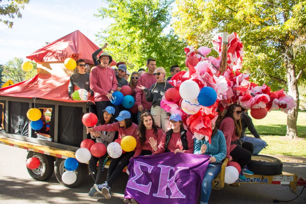 Students smiling and posing on a parade float with balloons and colorful decorations