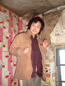 被迫害致疯的柳志梅,当有人试图接近,她就攥着双手躲向自家墙角(摄于二零一零年冬)