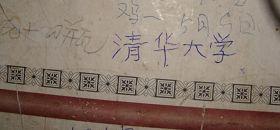 """柳志梅在自家破旧的瓦窑墙上,写下""""清华大学""""四个字。(摄于二零一零年冬)"""