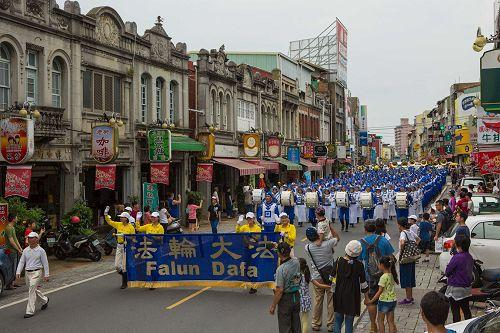 """'图1:台湾法轮大法天国乐团受邀参加了台南市政府举办一年一度的""""管乐艺术季""""开幕大游行,有不少民众拿出手机照相留影。'"""