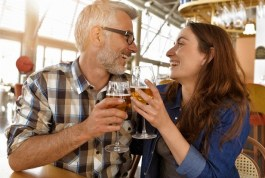 Couple,In,Bar,Cheering,With,Glass,Of,Beers