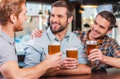 friends-in-bar-three-happy-young-men-in_bwc24346657