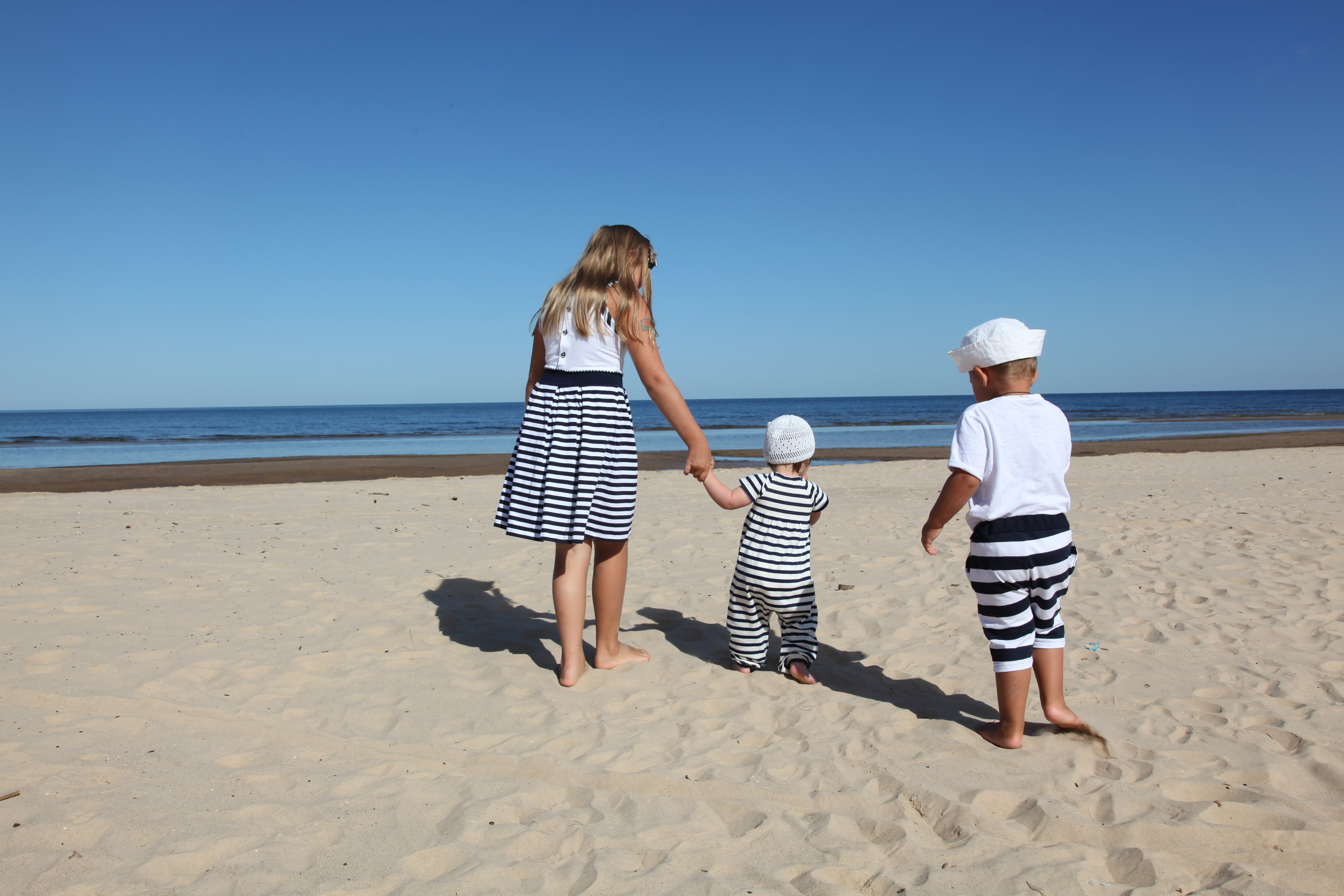 3 Children On A Beach Enjoying The Sunshine. By The Sea With Blue Sky