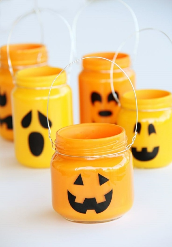 DIY halloween decoration ideas glass jars candle holder orange with face