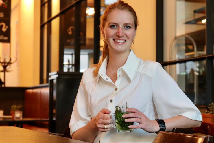 Marleen sitting in a cafe wearing a white blouse holding a cup of tea