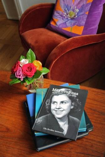 """En sammetsklädd fåtölj bakom ett soffbord med en blombukett och några böcker. Överst ligger Ulla Brodins memoar """"Mitt livs resa"""", skriven av Pia Hintze, producerad av Min Memoar."""