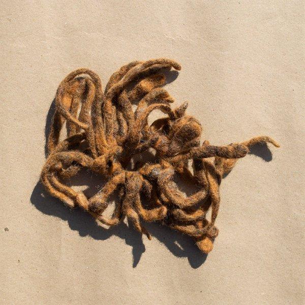 Rastarenksu-hiuslenkki, keltaruskeita villasuikaleita kiinnitettynä elastiseen hiuslenkkiin