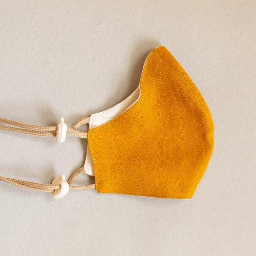 Pellavamaski stopparilla, keltainen-valkoinen.