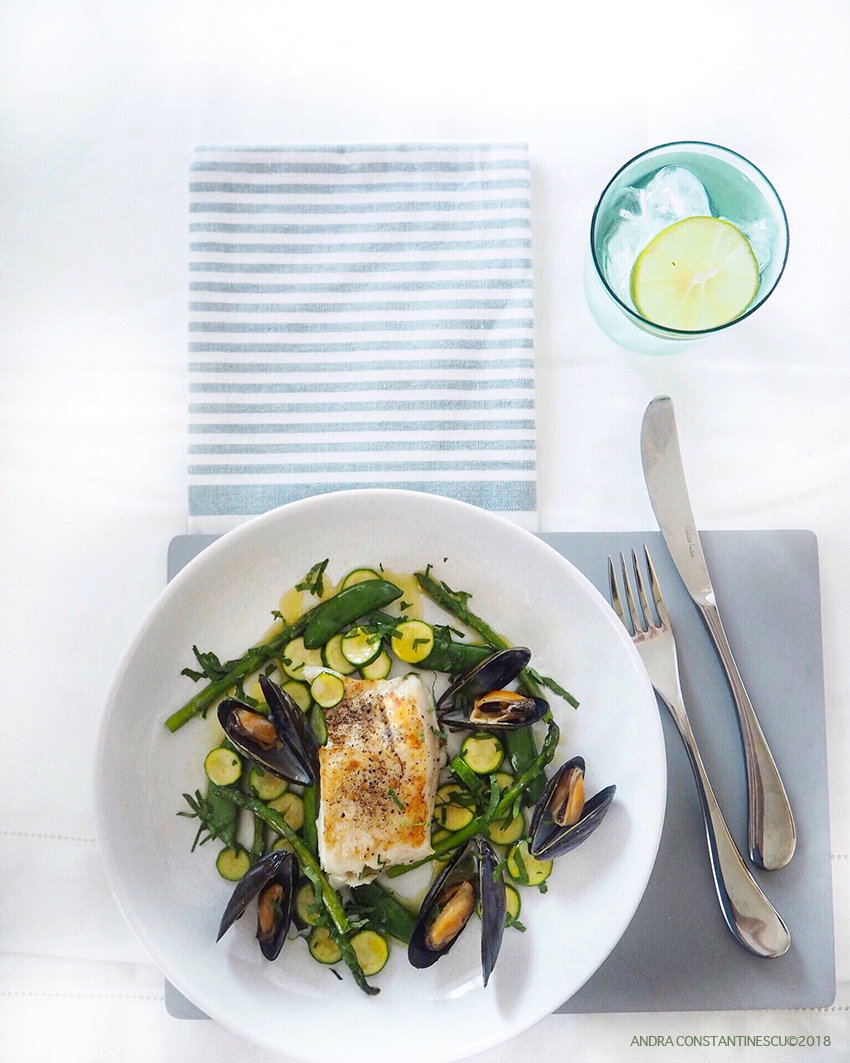 a plate of hake fillet with mussels and baby courgette ready to be served at lunch