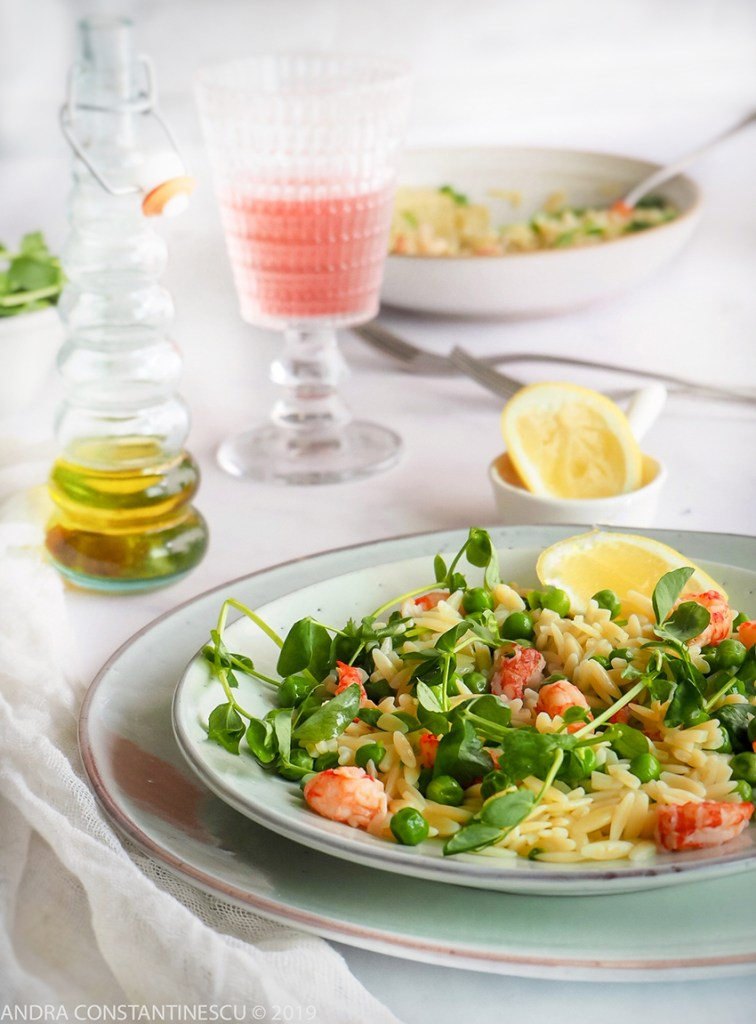 Orzo salad with crayfish and green peas served for lunch with a glass of rose wine.