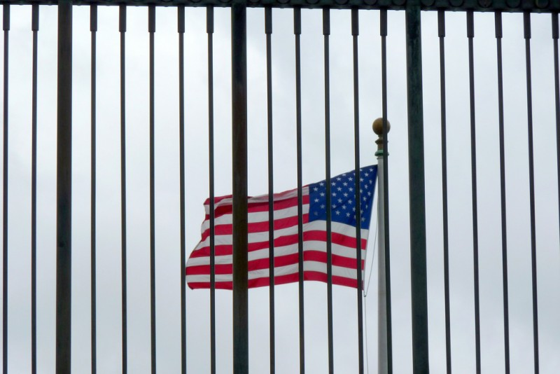 An American flag seen from behind a fence, so that it appears to be behind prison bars.