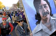 """Marchers carry a large painting of American Indian Leonard Peltier during a """"National Day of Mourning,"""" Thursday, Nov. 22, 2001, in Plymouth, Mass. (AP Photo/Steven Senne)"""