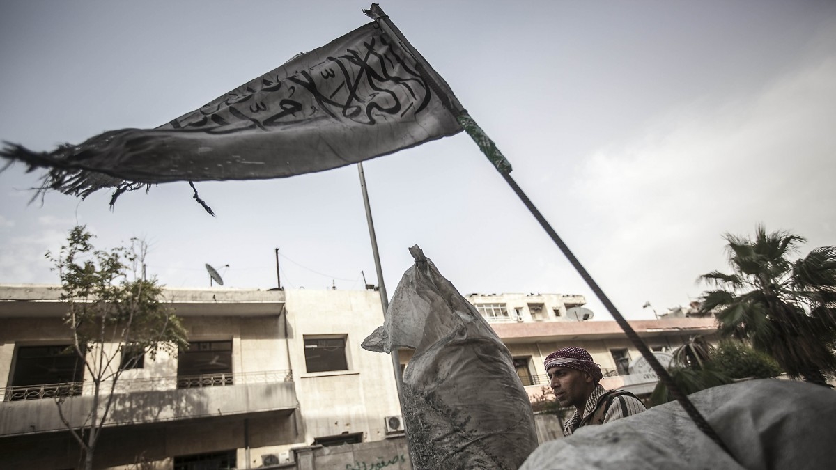 A rebel fighter stands guard at a check point flying a banner near the front line in Aleppo, when Syria rebels groups began fighting each other for control of a key checkpoint in the northern city of Aleppo. (Photo: Narciso Contreras/AP)