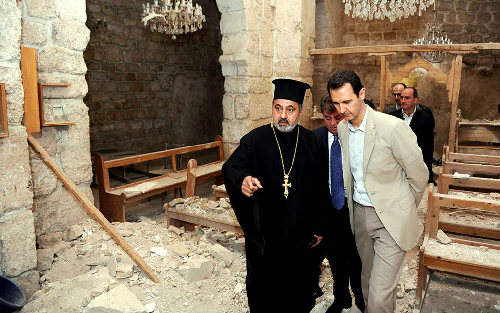 Syrian President Bashar al-Assad, right, checks a church damaged by militants during a visit to the Christian village of Maaloula, near Damascus, Syria. April 20, 2014. (Syrian Presidency via Facebook)