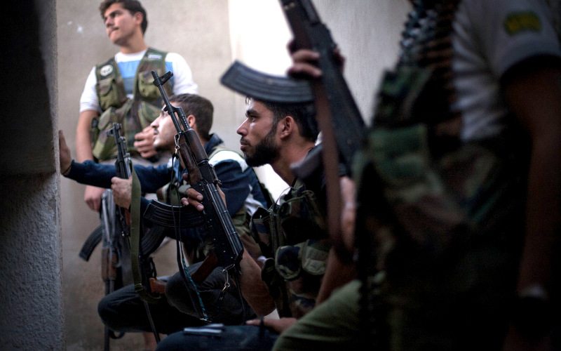 Free Syrian Army fighters take cover from incoming Syrian Army fire in the Izaa district in Aleppo, Syria, Wednesday, Sept. 12, 2012. (AP/Manu Brabo)