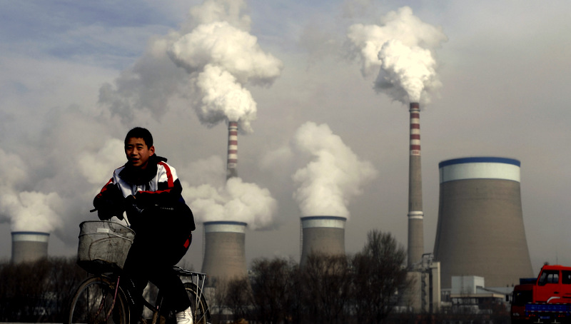 A Chinese boy cycles past a cooling towers of a coal-fired power plant in Dadong, Shanxi province, China.