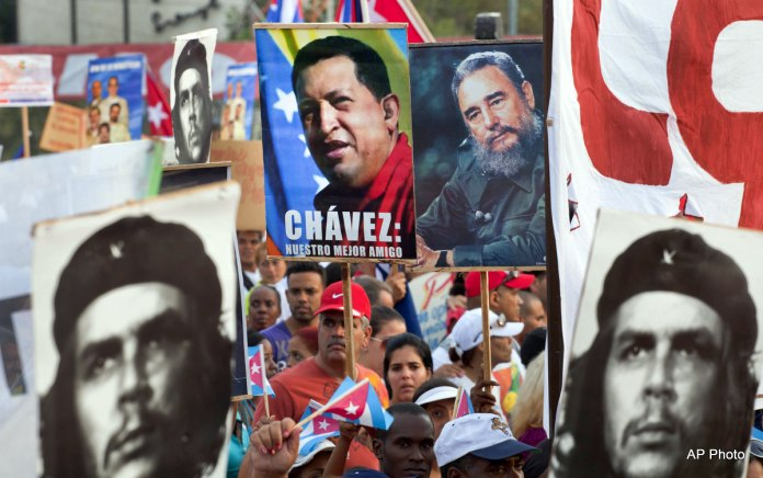 "People hold up images showing Fidel Castro, second from right, Venezuela's late President Hugo Chavez, center, and Cuba's revolutionary hero Ernesto 'Che' Guevara, bottom left and right, during a May Day march in Revolution Square in Havana, Cuba, Wednesday, May 1, 2013. The image of Chavez carries the words in Spanish ""Chavez : Our best friend."" (AP Photo/Ramon Espinosa)"