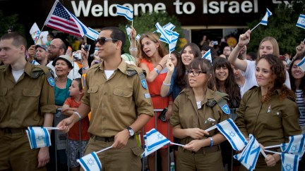 Israeli soldiers and relatives of new Jewish immigrants from the U.S. and Canada, wave Israeli flags to welcome them as they arrive at Ben Gurion airport near Tel Aviv, Israel, Tuesday, July 23, 2013. A total of 231 Jewish immigrants arrived on the flight from the U.S. Tuesday and were welcomed in a ceremony at the airport. Israel's Law of Return accords any Jew and eligible non-Jewish relatives the legal right to assisted immigration and settlement in Israel, as well as Israeli citizenship. (AP Photo/Ariel Schalit)