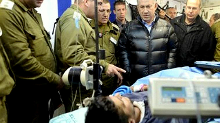 Netanyahu looks at a Syrian rebel fighter being treated in an IDF field hospital. (Photo: Kobi Gideon/GPO)