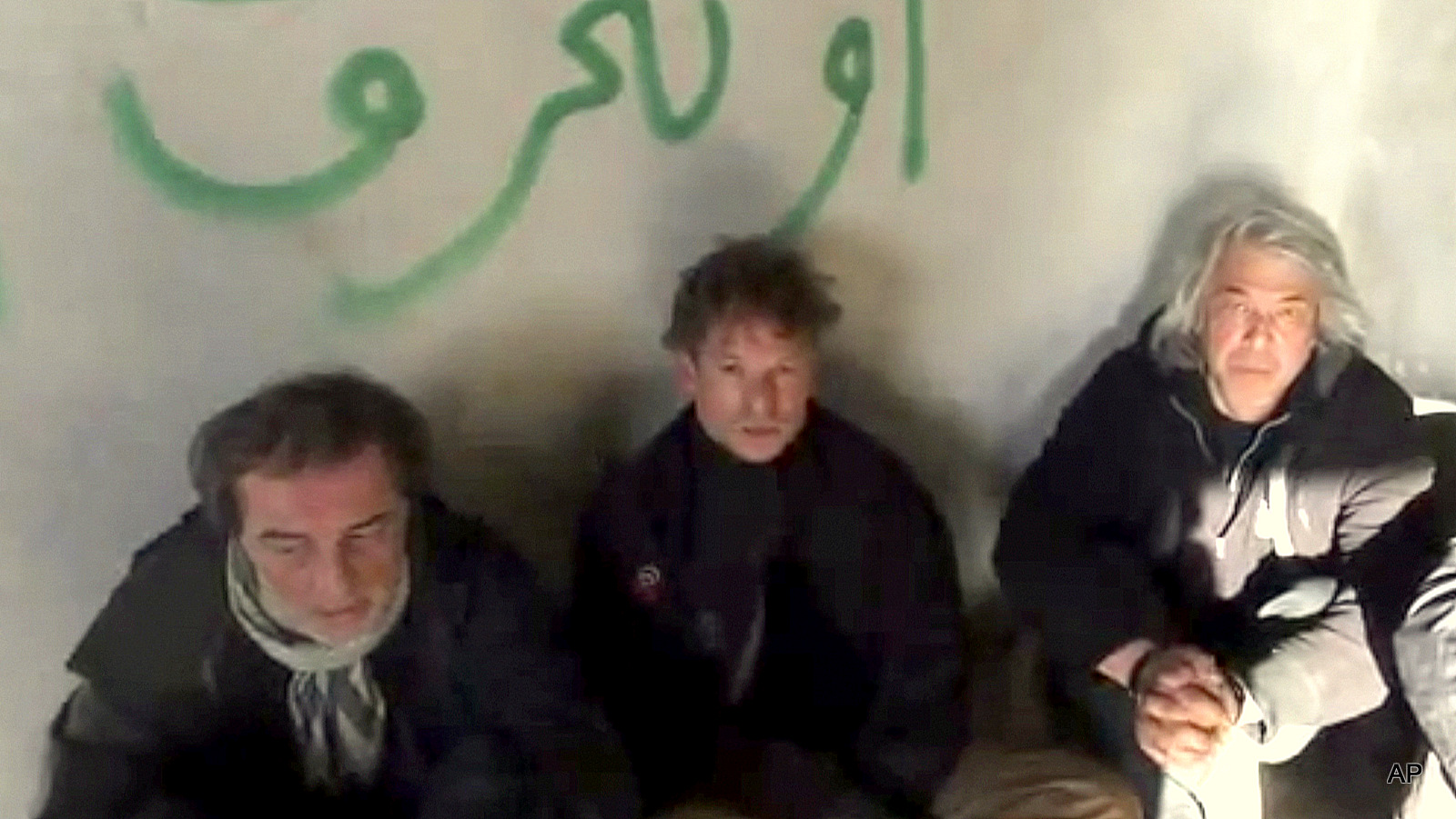 This image taken from undated amateur video posted on the Internet shows NBC chief foreign correspondent Richard Engel, center, with NBC Turkey reporter Aziz Akyavas, left, and NBC photographer John Kooistra, right, after they were taken hostage in Syria. More than a dozen heavily armed gunmen kidnapped and held Engel and several colleagues for five days inside Syria, keeping them blindfolded and tied up before they finally escaped unharmed during a firefight between their captors and anti-regime rebels, Engel claimed, but later admitted it was actually the rebels who carried out the kidnapping.