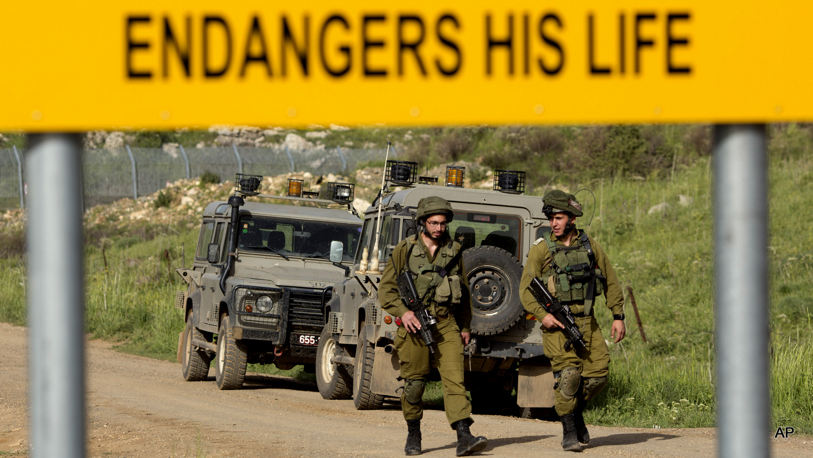 Israeli soldiers walks near the border with Syria near the site of a Sunday Israeli airstrike, in the Israeli controlled Golan Heights, Monday, April 27, 2015