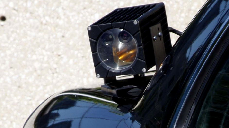 A camera mounted on the trunk of a police car  scans traffic on the streets, aggregating data such as patterns on travel and frequency of visits to a certain area.