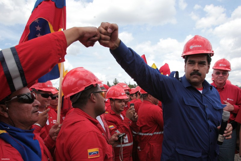 Venezuelan President Nicolas Maduro fist bumps a worker of the state-run oil company PDVSA during a visit to the Orinoco oil belt in Venezuela in 2013. Miraflores Presidential Office/AP/File