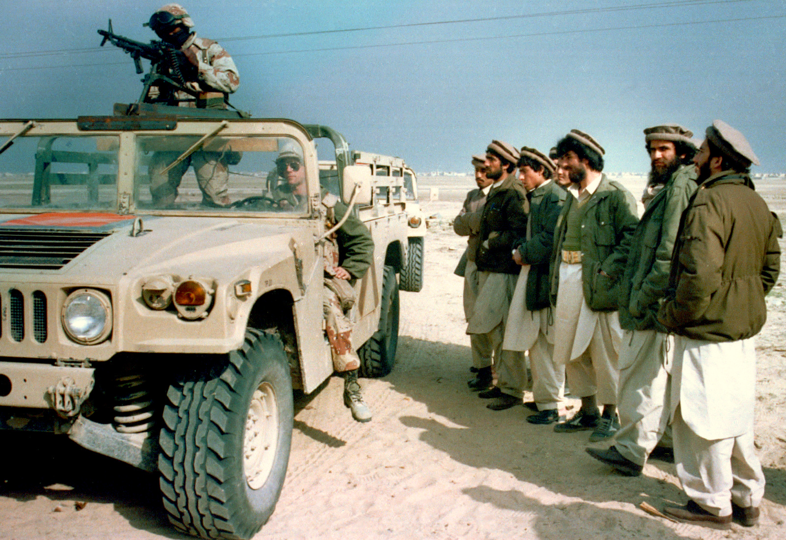 A group of Afghan mujahedeens, Islamic guerrillas, look over a U.S. Marine humvee in eastern Saudi Arabia, Monday, Feb. 11, 1991. The Marines visited a camp consisting of about 300 mujahedeens who have been asked by the Saudi government to help fight against Iraq in the Gulf War. (AP Photo/Department of Defense)