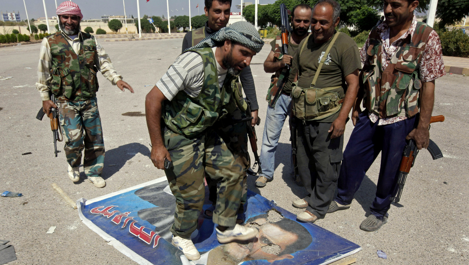 A Free Syrian Army fighter from the Al-Faruk brigade, center, steps on a portrait of Syrian President Bashar Assad, Sept. 22, 2012 (AP/Hussein Malla)