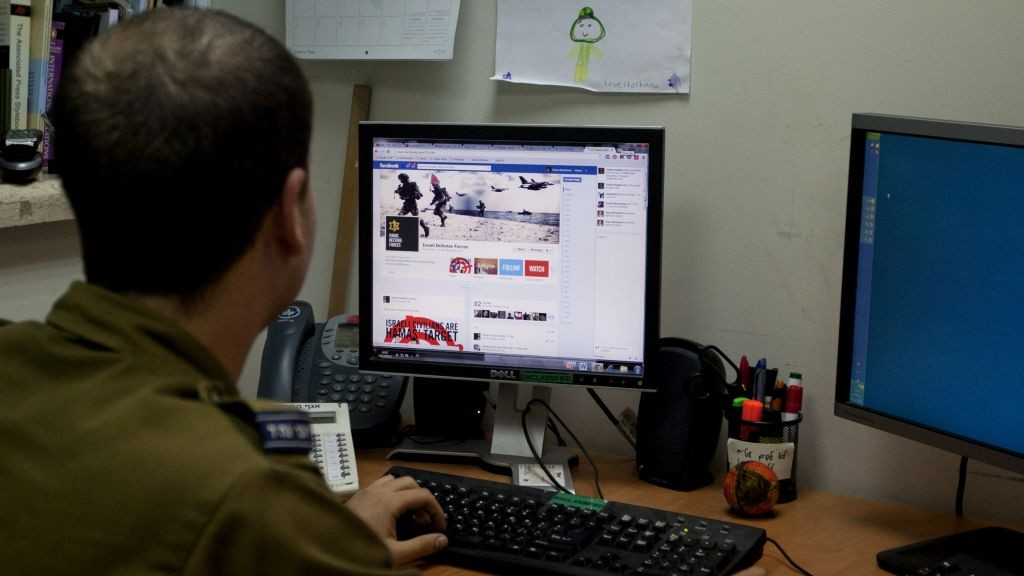 Am Israeli soldier looks at the IDF's Facebook page at the army spokesperson's office in Jerusalem.