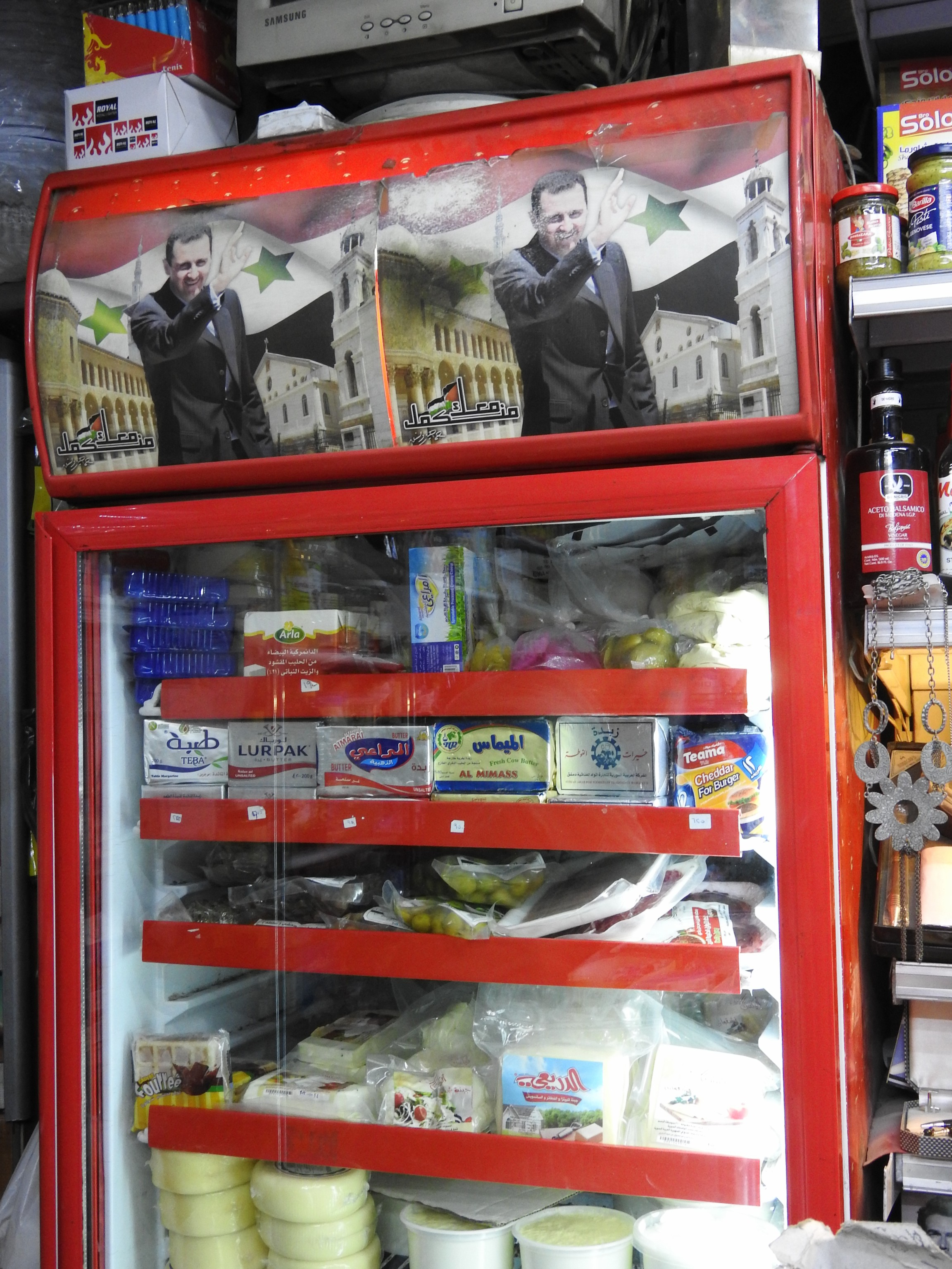 Stopping to buy water in an Old City shop, the owner's only issue with me taking a photograph of his fridge is that he wants to dust off the photos of President Assad a bit first, apologizing that they are old, from well-before the current crisis.