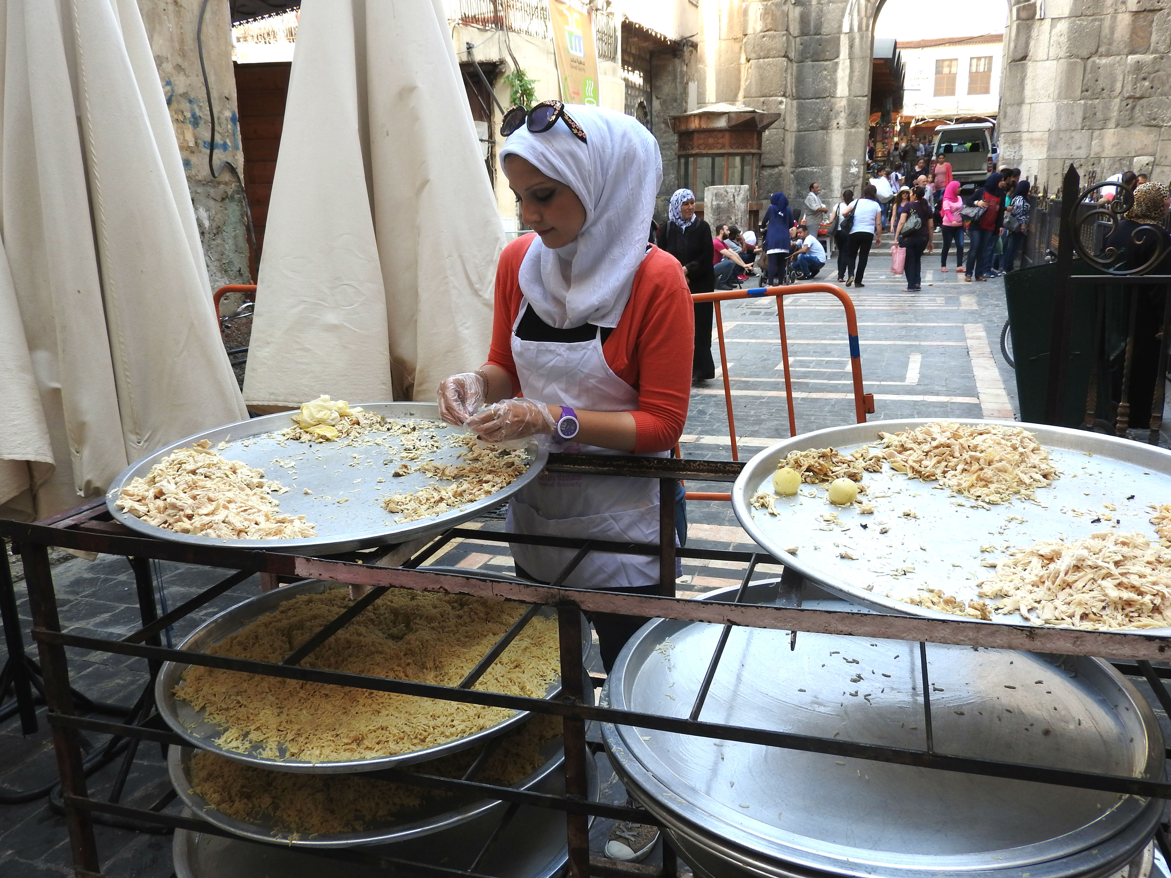 Behind the Umayyad Mosque in Old Damascus, one of tens of volunteers daily helps prepare the Iftar (fast-breaking) meals that the Saaed Association was serving to impoverished Damascus residents, even delivering to those unable to pick up meals themselves. Starting with 3,000 recipients, by the end of Ramadan, the volunteers were providing 10,000 meals daily in Damascus alone, with another combined 7,000 meals prepared in Hama and Homs.