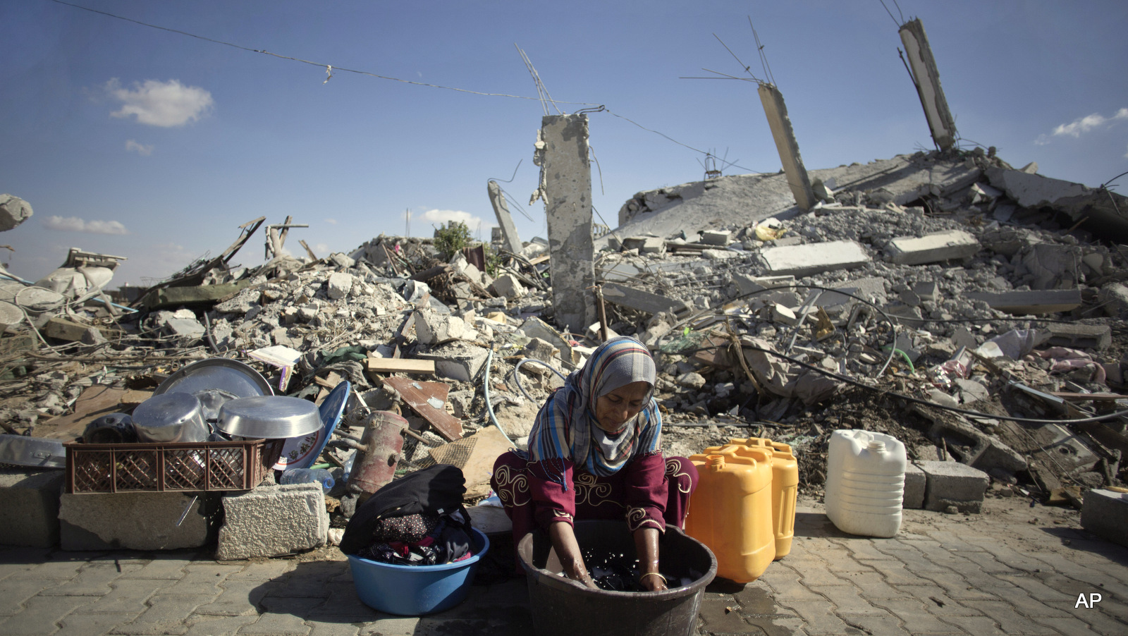 A woman washes clothes as she sits in front of the rubble of her family house in Khuzaa, southern of Gaza Strip.