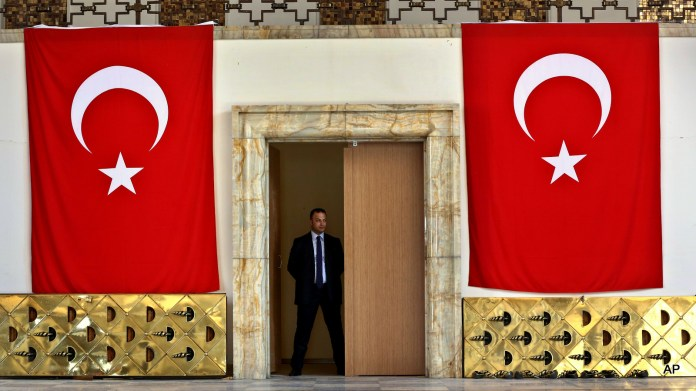 A Turkish parliament security man stands guard next to the broken yellow copper doors laid on the ground at the entrance of the assembly hall at the parliament building which was attacked by the Turkish warplanes during the failed military coup last Friday, in Ankara, Turkey, Tuesday, July 19, 2016.