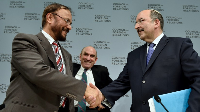 Dore Gold and Anwar Eshki shake hands at a CFR event, as Elliott Abrams looks on.