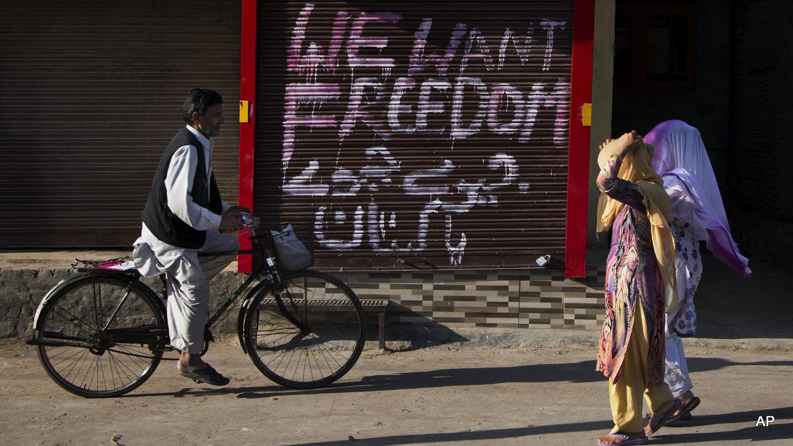 "Kashmiri women walk past a closed market with graffiti painted on the shutter of a shop in Urdu that reads ""Long live Pakistan"" in Srinagar, Indian occupied Kashmir, Thursday, Sept. 29, 2016."