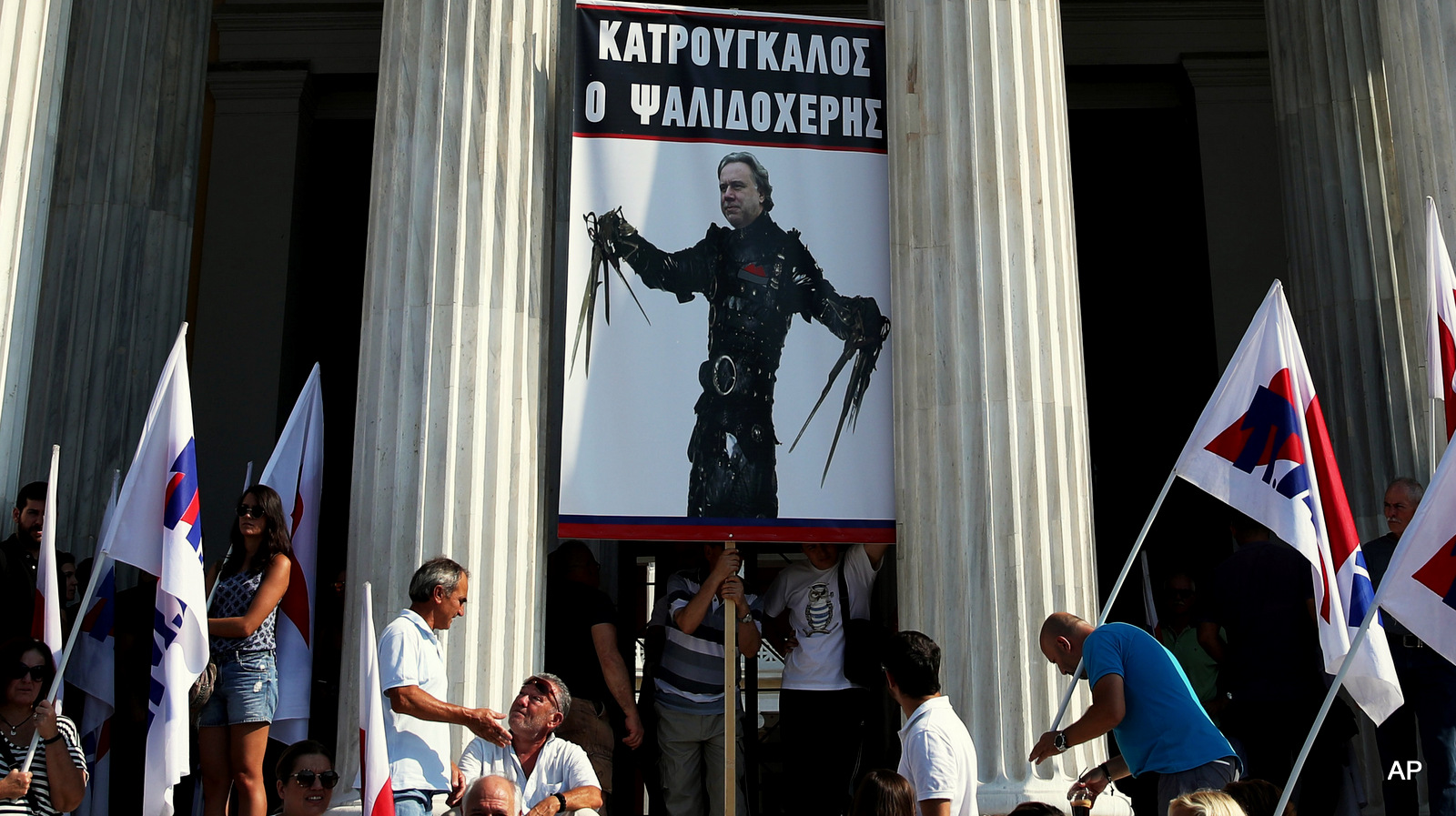 "Protesters against new austerity measures hold a placard depicting Labour Minister George Katrougalos as the movie character Edward Scissorhands during a protest outside Zappeion Hall in Athens, Friday, Sept. 16, 2016. The placard reads in Greek""Katrougalos Scissorhands""."