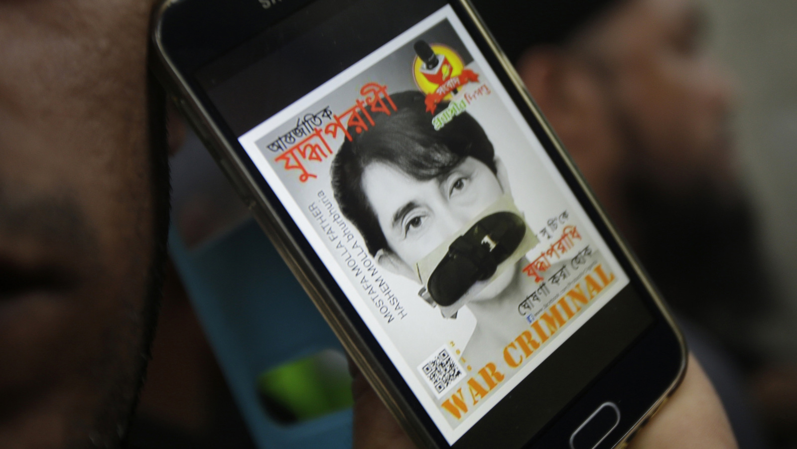 A portrait of Myanmar's Foreign Minister Aung San Suu Kyi with her mouth covered with a sandal displayed on a mobile phone screen is shown by a protester during a demonstration in front of the Myanmar Embassy in Bangkok, Thailand, Friday, Nov. 25, 2016 against the murder, displacement and persecution of Muslim Rohingya in Myanmar. (AP Photo/Sakchai Lalit)