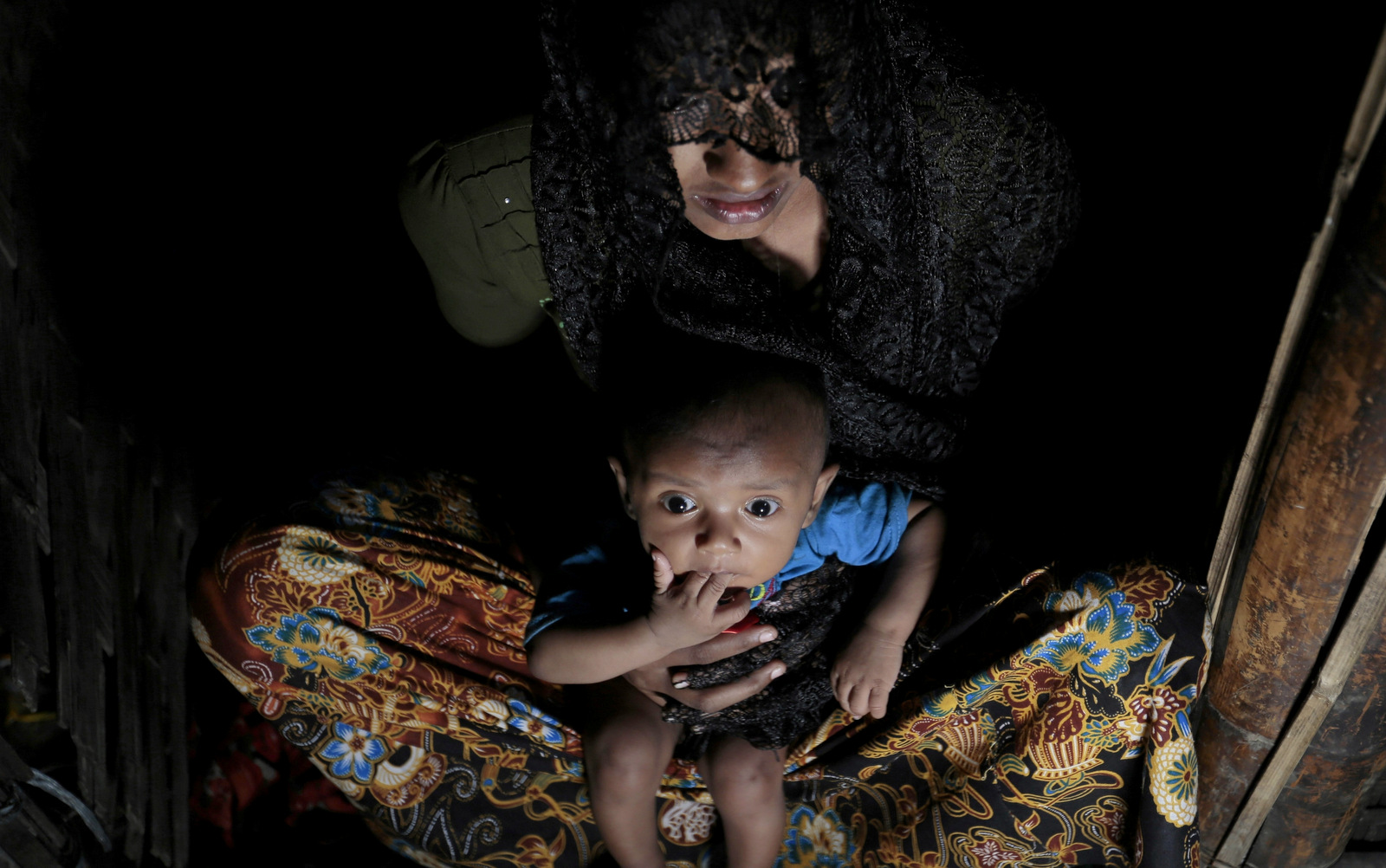 Mohsena Begum, a Rohingya who escaped to Bangladesh from Myanmar, holds her child and sits at the entrance of a room of an unregistered refugee camp in Teknaf, near Cox's Bazar, a southern coastal district about, 296 kilometers (183 miles) south of Dhaka, Bangladesh. Dec. 2, 2016. (AP Photo/A.M. Ahad)