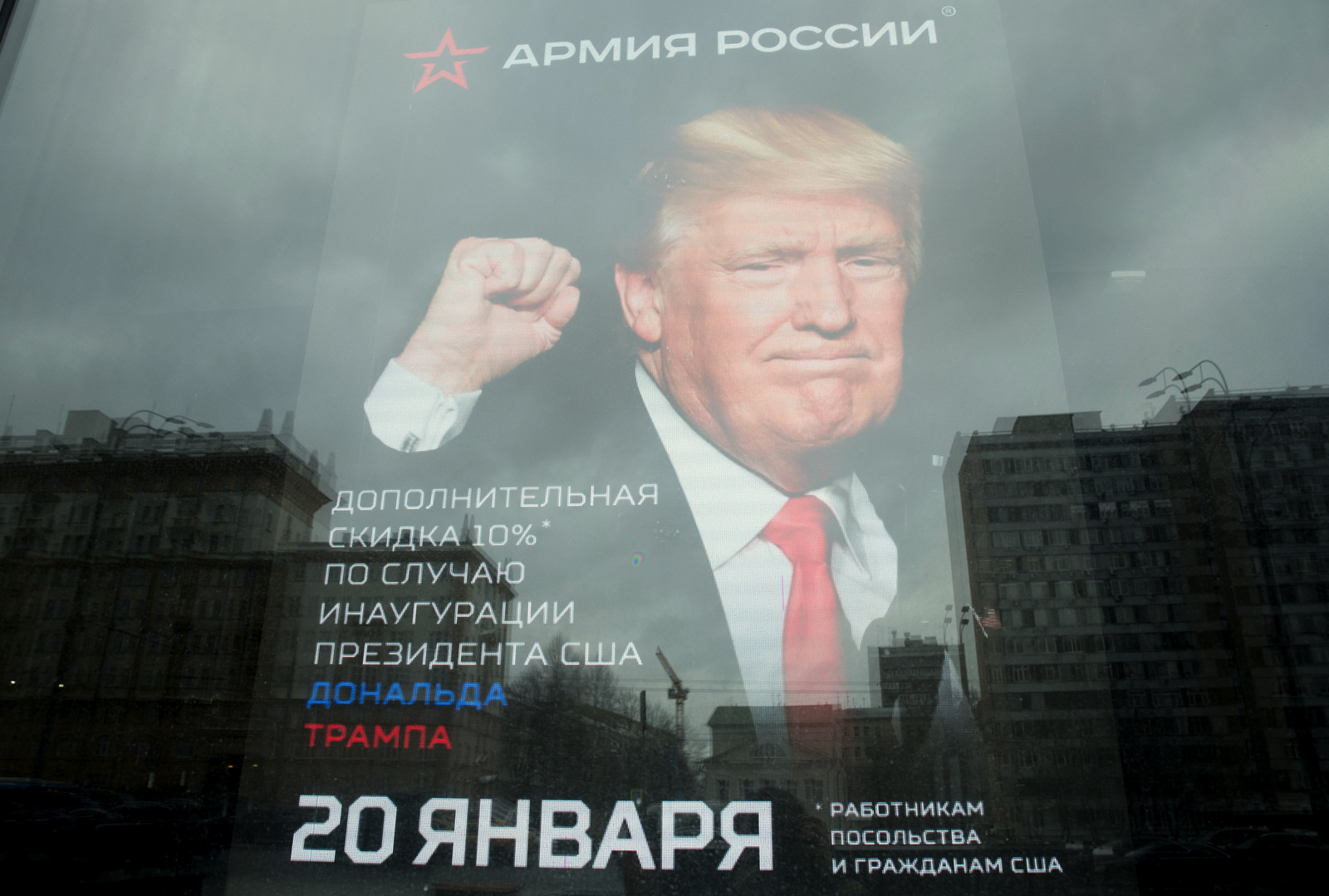 """The U.S. Embassy building is reflected in a window of a Russian military outerwear shop """"Armia Rossii"""" (Russian Army) displaying a poster of Donald Trump, in downtown Moscow, Russia, Friday, Jan. 20, 2017, hours ahead of Donald Trump being sworn in as president of the United States, The poster reads: """"10 percent discount to the embassy employees and US citizens on the Inauguration Day"""". (AP/Pavel Golovkin)"""