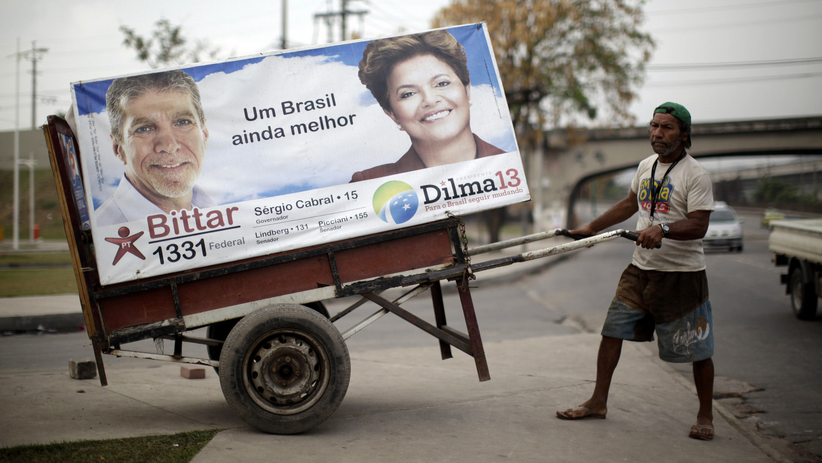 A man pulls a cart with an electoral poster of Workers Party presidential candidate Dilma Rousseff, right, at Manguinhos slum in Rio de Janeiro, Brazil, Wednesday, Sept. 29, 2010. (AP/Felipe Dana)