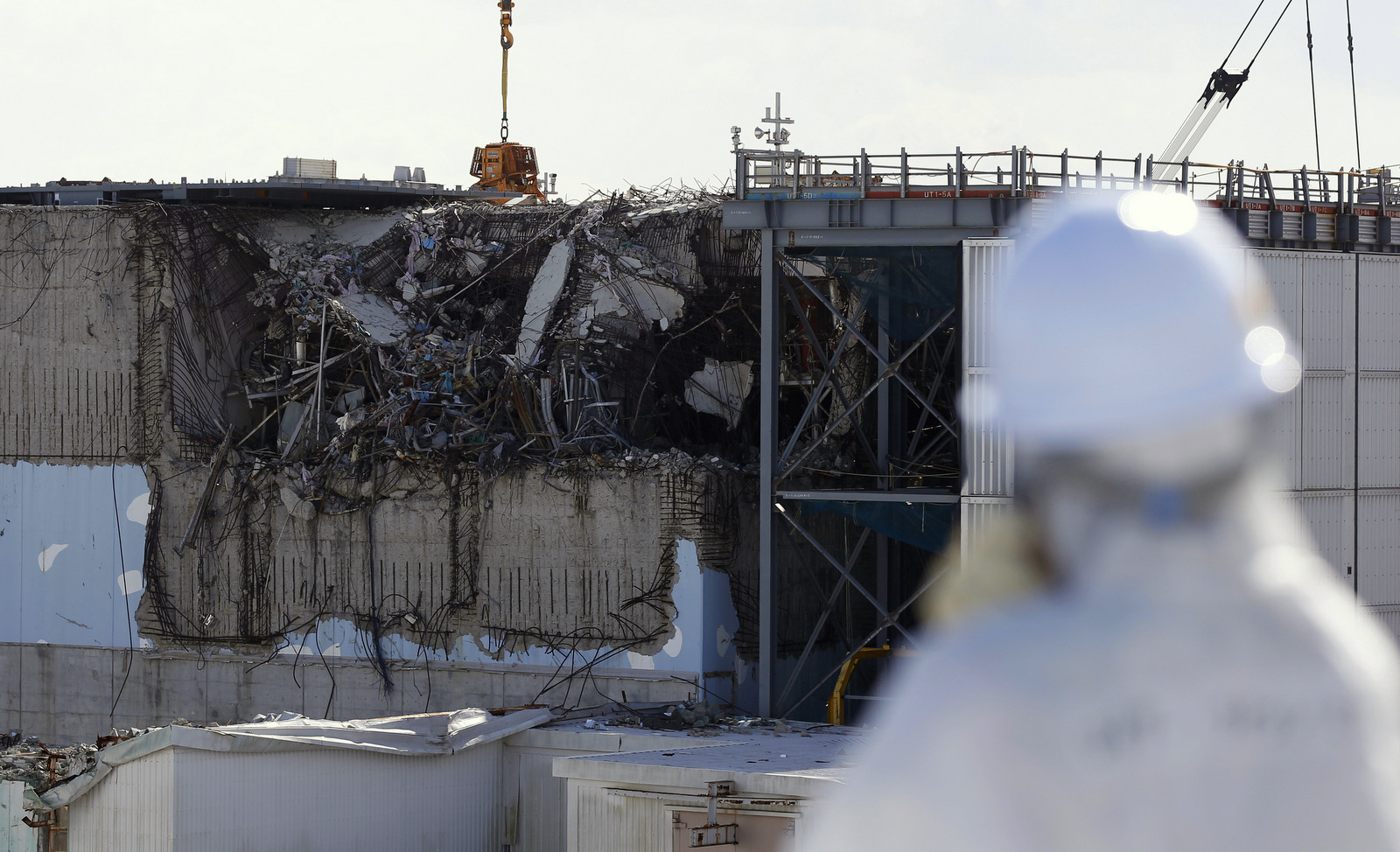 A member of the media tour group wearing a protective suit and a mask looks at the No. 3 reactor building at Tokyo Electric Power Co's (TEPCO) tsunami-crippled Fukushima Dai-ichi nuclear power plant in Okuma, Fukushima Prefecture, northeastern Japan, Wednesday, Feb. 10, 2016. (Toru Hanai/AP)