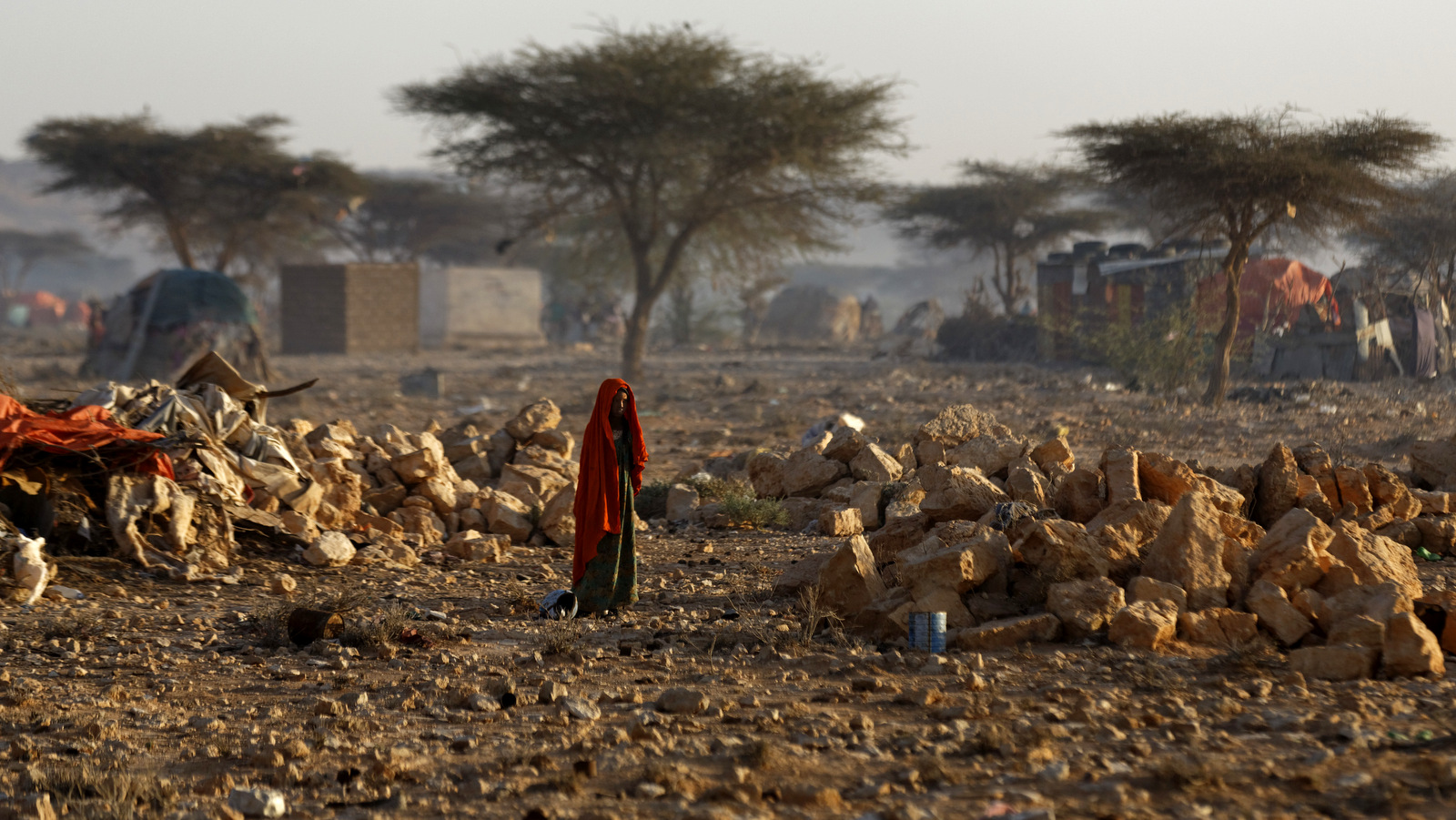 A Somali woman walks through a camp of people displaced from their homes elsewhere in the country by the drought, shortly after dawn in Qardho, Somalia Thursday, March 9, 2017. (AP/Ben Curtis)