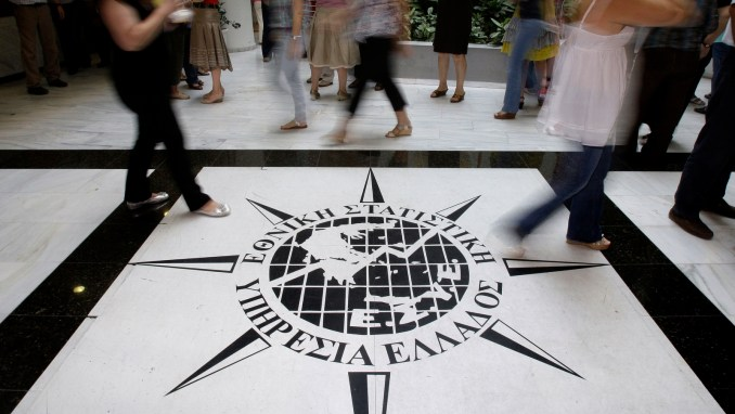 Greece's Statistics agency employees walk past the logo of the agency in Piraeus, near Athens. Serious errors in Greek deficit data, revealed last year, helped trigger the European government debt crisis rattled world markets and confidence in the euro. (AP/Petros Giannakouris)