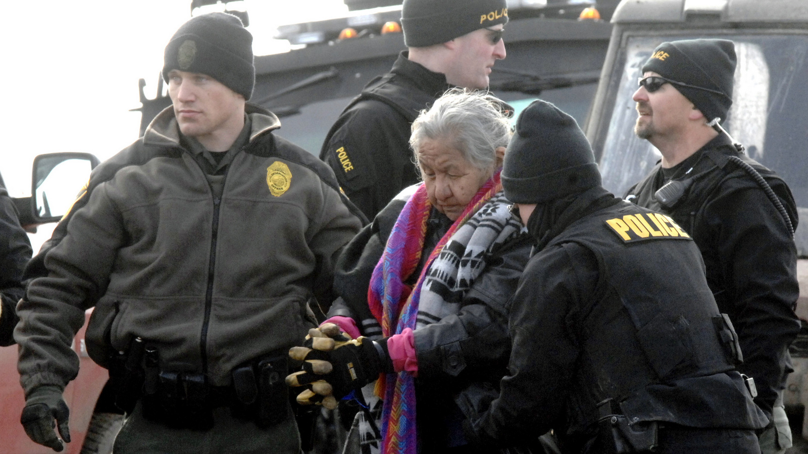 An elderly woman is escorted to a transport van after being arrested by law enforcement at the Oceti Sakowin camp as part of the final sweep of the Dakota Access pipeline protesters in Morton County, Feb. 23, 2017, near Cannon Ball, N.D. (Mike McCleary/The Bismarck Tribune)