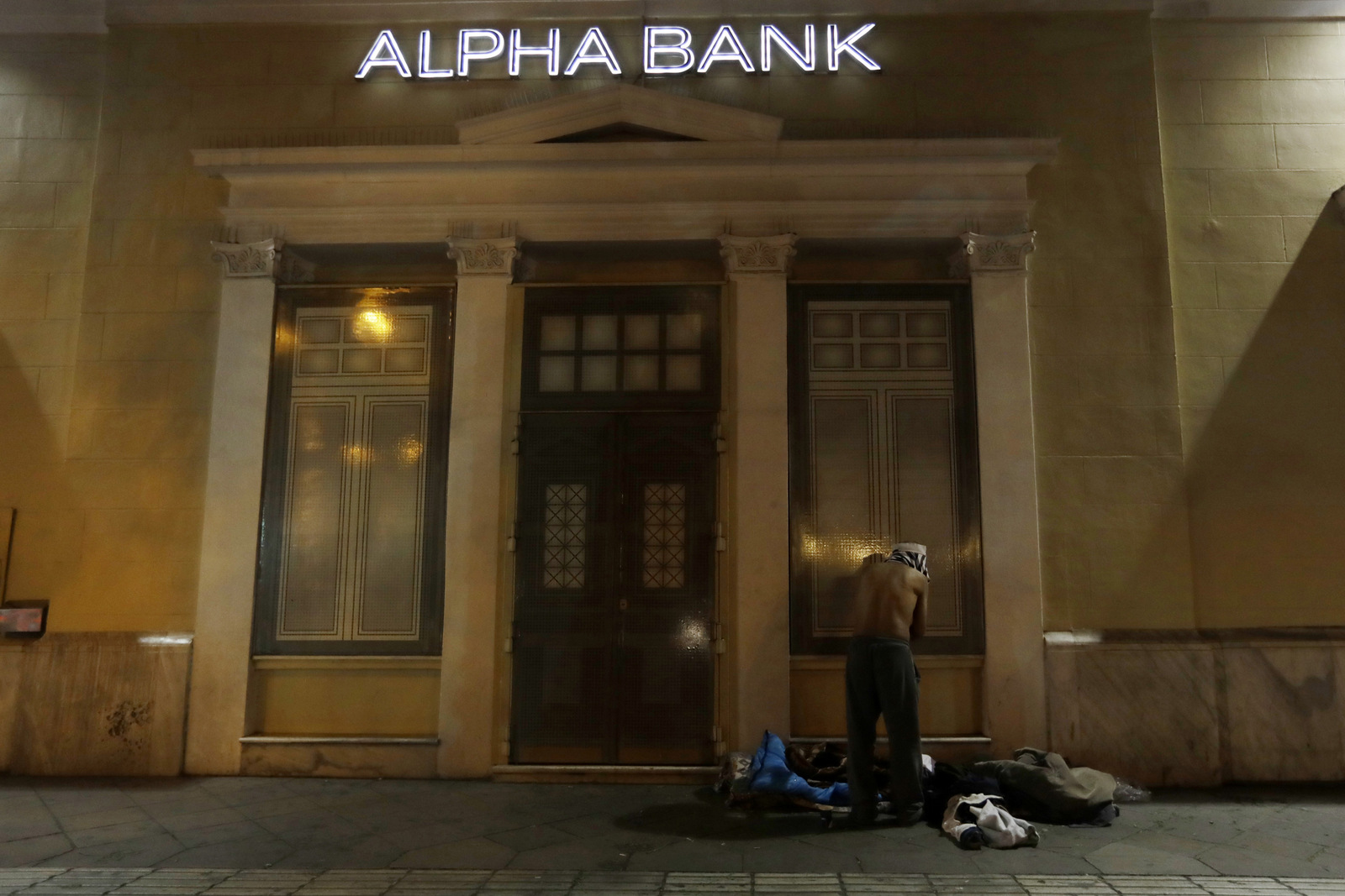 A homeless person changes clothes outside a bank in central Athens. Nearly one-in-four Greeks are unemployed and receive no benefits. Poverty rates have surged here since the start of the crisis in late 2009, with nearly 36 percent of the country living in financial distress. (AP/Thanassis Stavrakis)