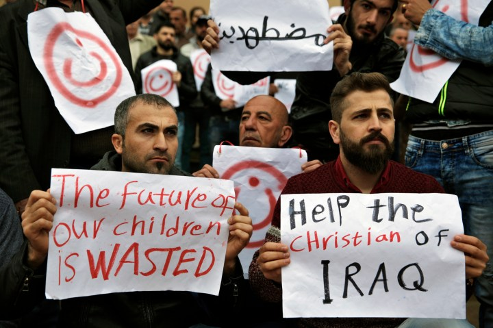 Iraqi Christians who live in Lebanon hold placards during a sit-in, in front of the United Nations Headquarters demanding speeding up their immigration cases in Beirut, Lebanon, Feb. 13, 2017. Thousands of Christians from Iraq and Syria have fled violence in their country and sought refuge in Lebanon, a religiously-mixed country. The placard in Arabic reads