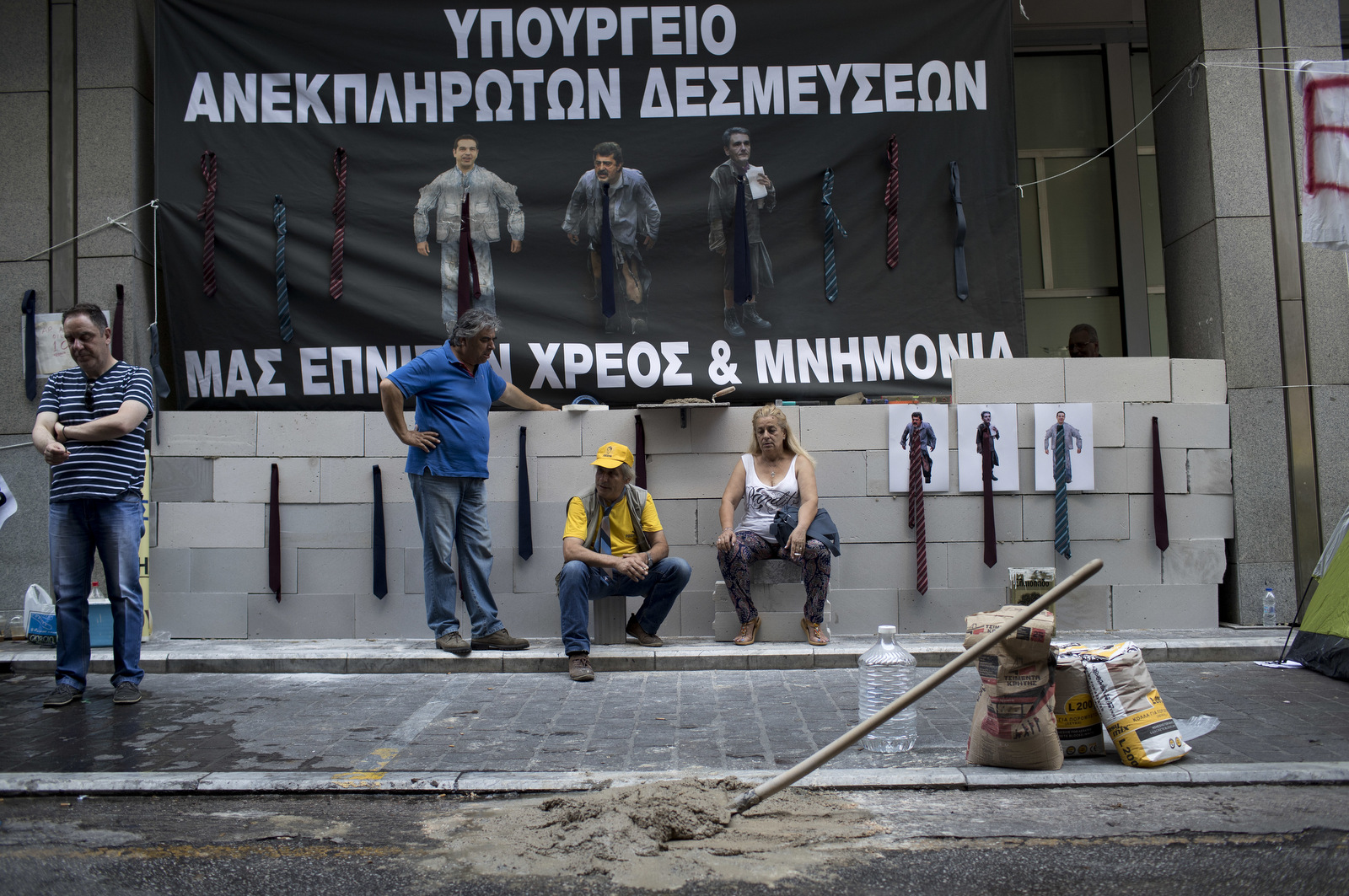 """Protesting hospital staff sit in front of a wall that they built at the entrance of the Greek Finance Ministry with a banner depicting Greek Prime Minister Alexis Thipras , Deputy Health Minister Pavlos Polakis and Greek Finance Minister Euclid Tsakalotos wearing ties reading in Greek ''Ministry of broken promises"""" and """" We drown in debt and bailouts"""" in central Athens. (AP/Petros Giannakouris)"""