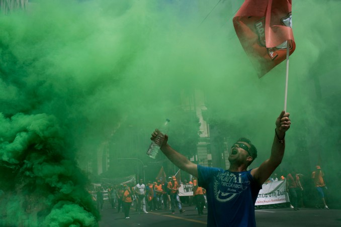 A protester reacts next to a flare outside the the Interior Ministry as thousands of striking municipal workers demonstrate in central Athens, June 22, 2017. Union officials want the left-led government to grant full-time, permanent state jobs to municipal workers employed on short-term contracts that have expired or are about to expire. (AP/Petros Giannakouris)